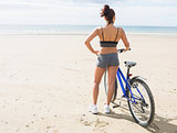 Rear view of a woman with bike on beach