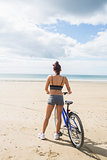 Slender woman standing with bike on the beach