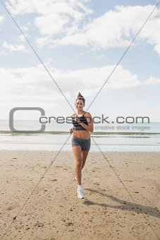 Sporty brunette woman jogging on the beach