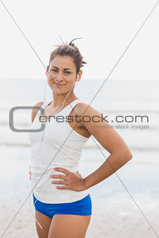 Woman listening to music through earphones at beach