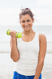Cheerful smiling woman lifting dumbbells standing on beach