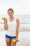 Cute content woman lifting dumbbells on the beach
