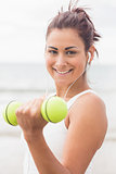 Cute smiling woman lifting dumbbells on the beach