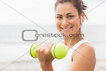 Calm sporty woman lifting dumbbells smiling at camera
