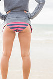 Slender woman in bikini bottom and gray jacket at beach