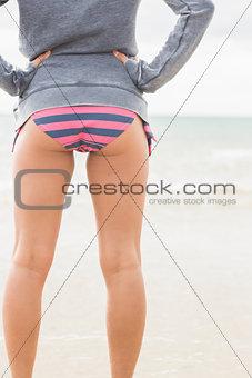 Slender woman in bikini bottom and gray jacket at beach