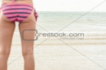 Mid section of a woman in striped bikini bottom at beach