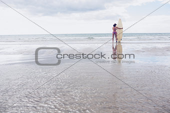 Calm woman in bikini with surfboard on beach