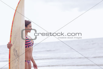 Beautiful woman in bikini with surfboard on beach