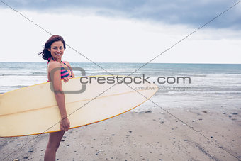 Smiling woman carrying surfboard on the beach