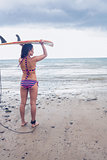 Bikini woman carrying surfboard on head at beach