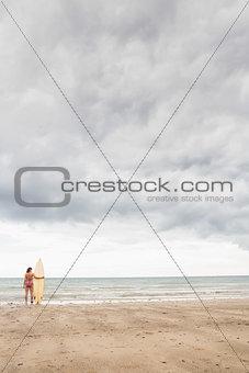Calm woman in bikini with surfboard on beach