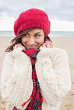Woman in stylish warm clothing looking away at beach