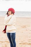 Cute woman in stylish warm clothing at beach