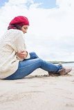 Woman in stylish warm clothing sitting at beach