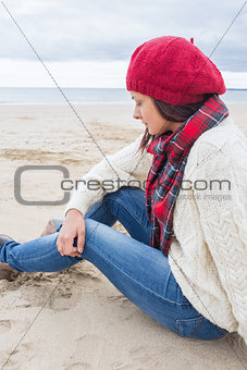 Woman in stylish warm clothing sitting at the beach