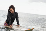 Smiling woman with surfboard in the water