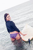 Rear view of a smiling woman with surfboard in water