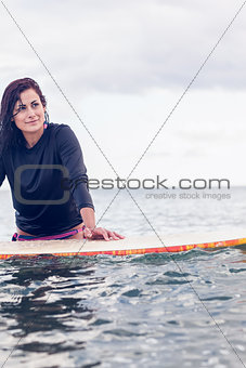 Beautiful young woman with surfboard in water