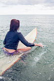 Rear view of a woman sitting on surfboard in water