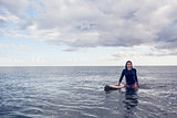 Portrait of a beautiful young woman with surfboard in water