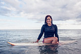 Portrait of a beautiful woman sitting on surfboard in water