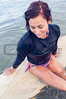 Beautiful young woman sitting on surfboard in water