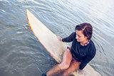 Beautiful woman sitting on surfboard in water
