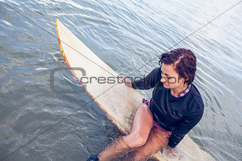 Beautiful woman sitting on surfboard in water