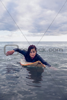 Woman swimming over surfboard in water