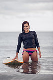 Portrait of a smiling woman with surfboard in water