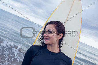 Beautiful woman looking away with surfboard at beach