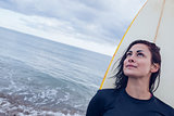 Beautiful woman looking up with surfboard