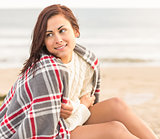 Beautiful woman covering herself with blanket at beach