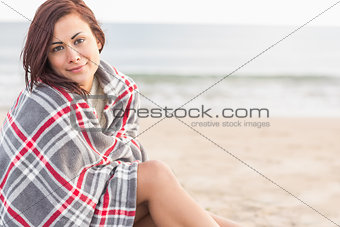 Portrait of a woman covered with blanket at beach