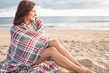 Side view of a woman covered with blanket at beach