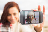 Woman self photographing with smartphone