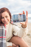 Woman self photographing with smartphone on beach