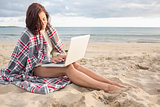 Woman covered with blanket using laptop at beach