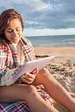 Woman covered with blanket using tablet PC at beach