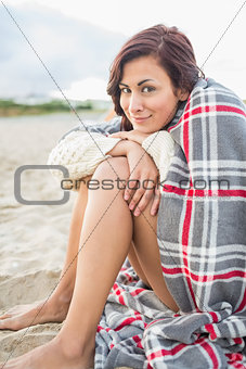 Woman covered with blanket at beach