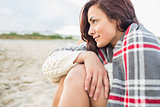 Side view of woman covered with blanket at beach