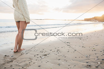 Low section of a woman in sweater standing on beach
