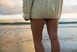 Mid section of woman in sweater standing on beach