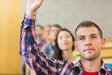 Close up of a male student raising hand by others in classroom