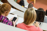 Females using laptop and cellphone in the lecture hall