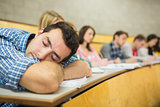 Male sleeping with students in lecture hall