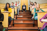 Rlegant teacher with students sitting at the lecture hall