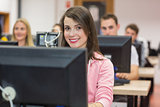 Smiling female student with others in the computer room