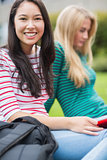 Smiling college student with blurred friend sitting in park
